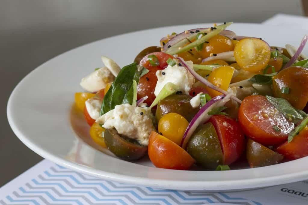 סלט קפרזה- עגבניות שרי צבעוניות, מוצרלה טרייה, בצל סגול, עלי בזיליקום ובלסמי  (צילום אנטולי מיכאלו)